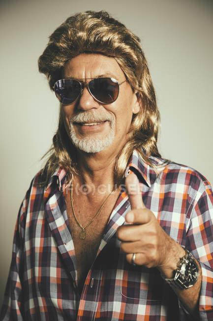 Retrato de hombre sonriente que lleva gafas de sol y una peluca rubia mostrando los pulgares para arriba - foto de stock