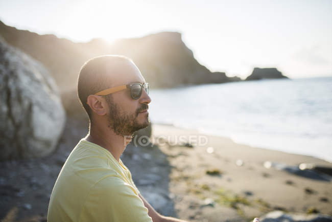 Man with sunglasses on the beach at backlight — Stock Photo