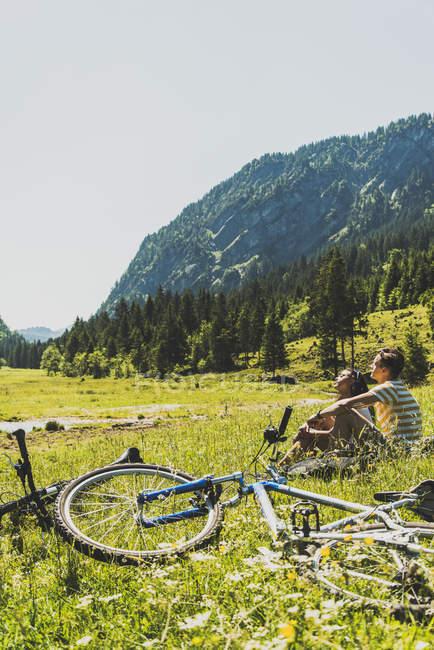 Austria, Tirol, Valle de Tannheim, pareja joven/esposos con bicicletas de montaña en Prado - foto de stock