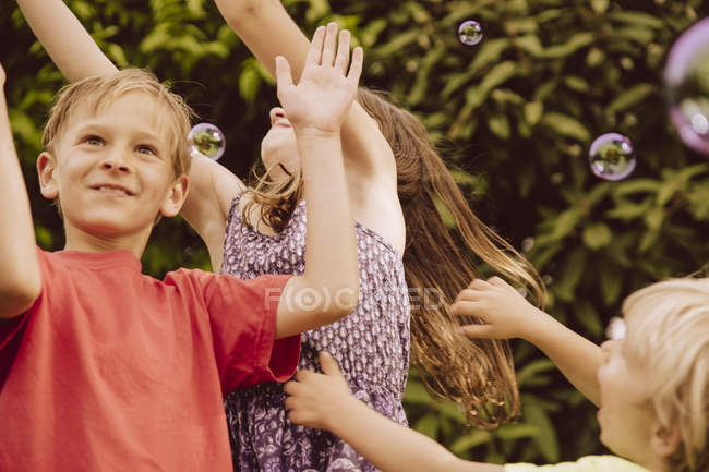 Three children playing with blow soap bubbles in garden — Stock Photo