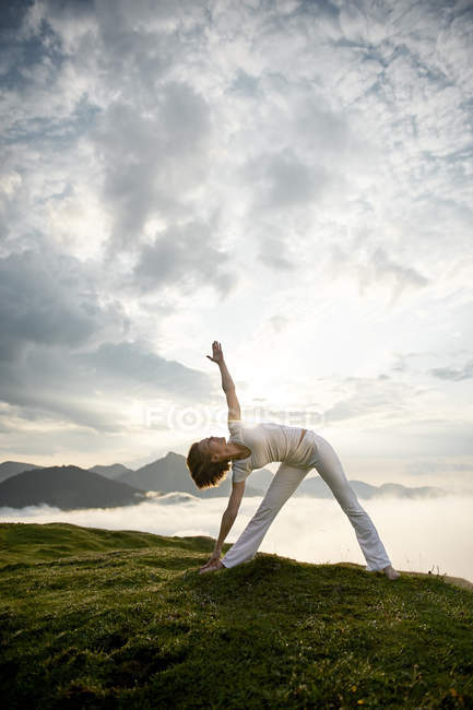 Austria.Kranzhorn, Mid adult woman practising yoga on mountain top — Stock Photo