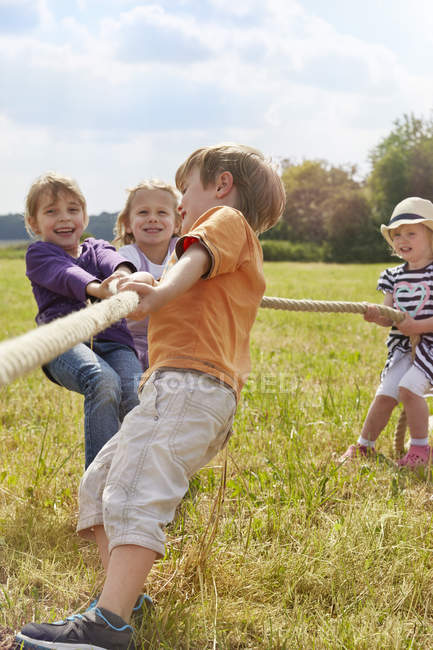 Дети дошкольника, потянув веревку на лугу — стоковое фото