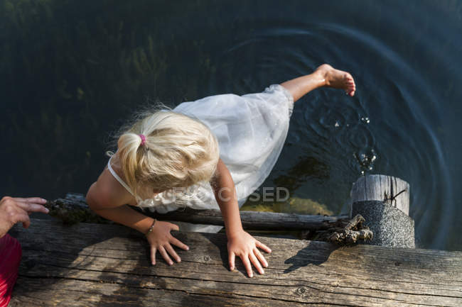 Girl in summer dress with foot in a lake — Stock Photo