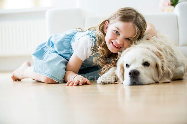 Bambina che stringe a sé con il suo cane, sdraiato sul pavimento — Foto stock