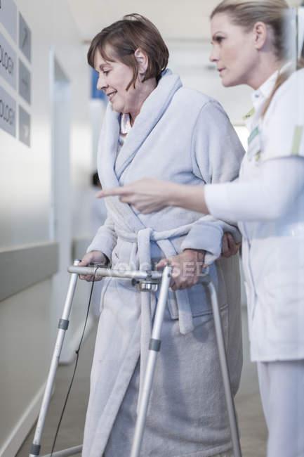 Krankenschwester hilft Patienten mit walking Frame im krankenhausflur — Stockfoto
