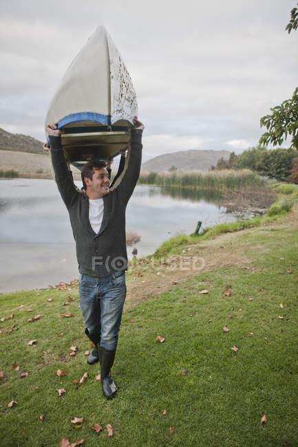 Homme portant un canot devant un lac — Photo de stock