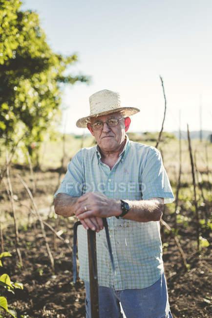 Porträt eines älteren Mannes, der sich auf eine Hacke stützt — Stockfoto