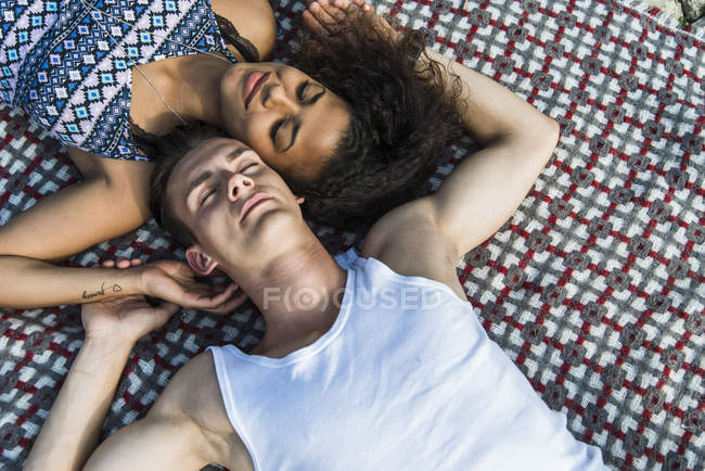 Relaxed young couple lying on blanket — Stock Photo