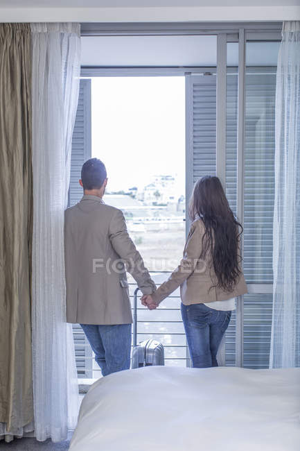 Back view of couple standing hand in hand in a hotel room — Stock Photo