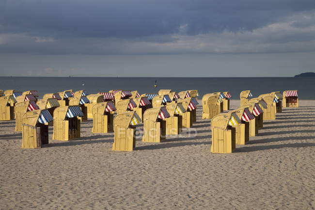 Germany, Luebeck Travemuende, view to beach with hooded beach chairs — Stock Photo