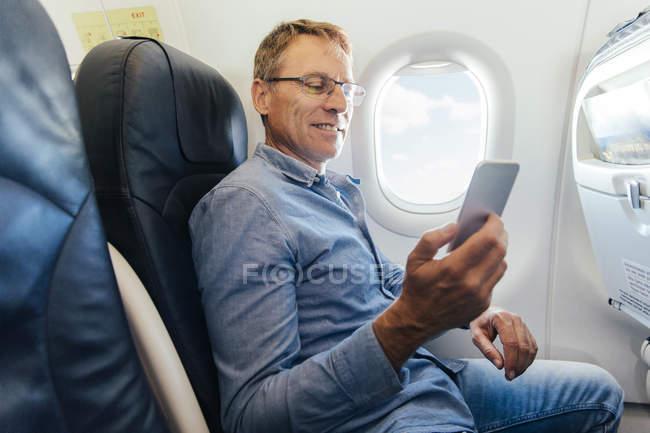 Homem maduro sentado em um avião olhando para seu smartphone — Fotografia de Stock