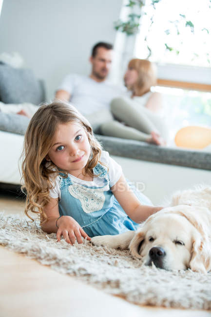 Bambina coccole con il suo cane, sdraiata sul pavimento, genitori in background — Foto stock