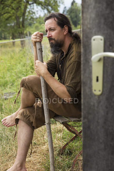 Man sitting with hiking pole at wooden hut — Stock Photo