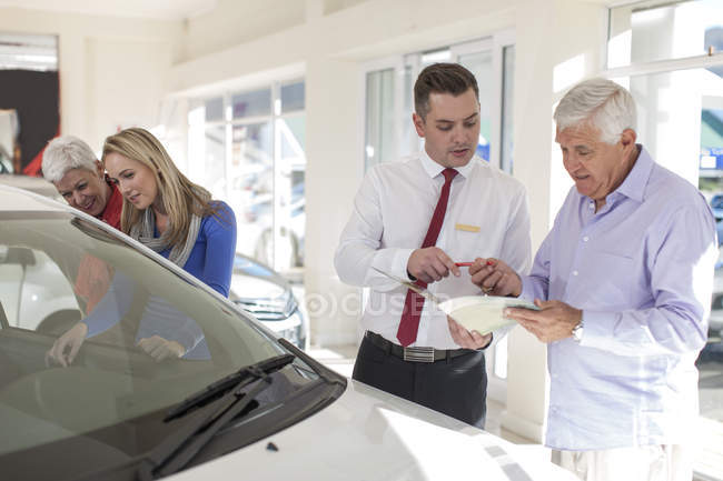 Senior man signing sales contract at car dealer — Stock Photo