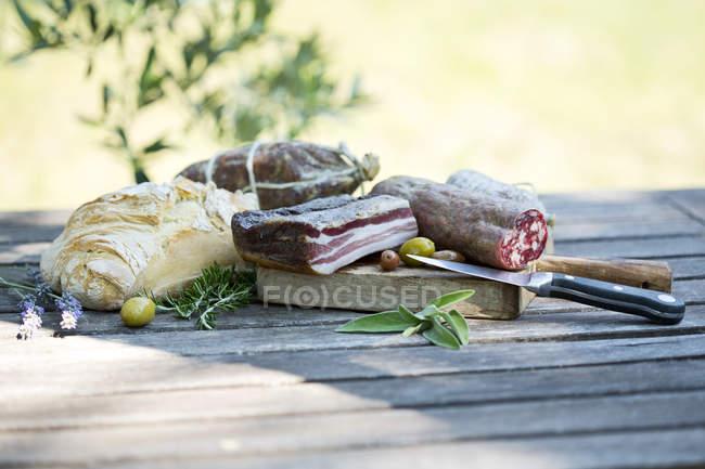 Панчетта, различные колбасы, хлеба и оливки на деревянный стол на открытом воздухе — стоковое фото