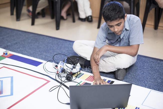 Schoolboy with laptop in robotics class testing vehicle on test track — Stock Photo