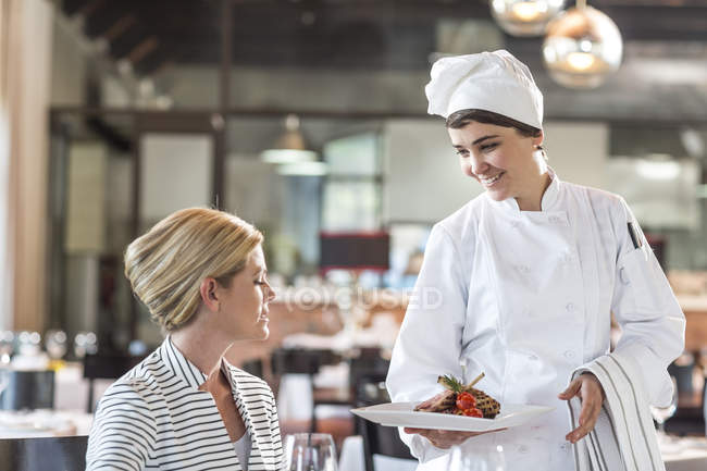 Female chef serving food for blonde woman — Stock Photo