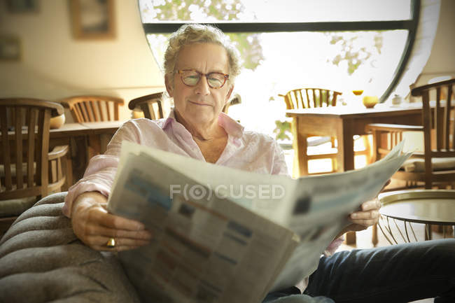 Smiling senior man in lounge room reading newspaper — Stock Photo