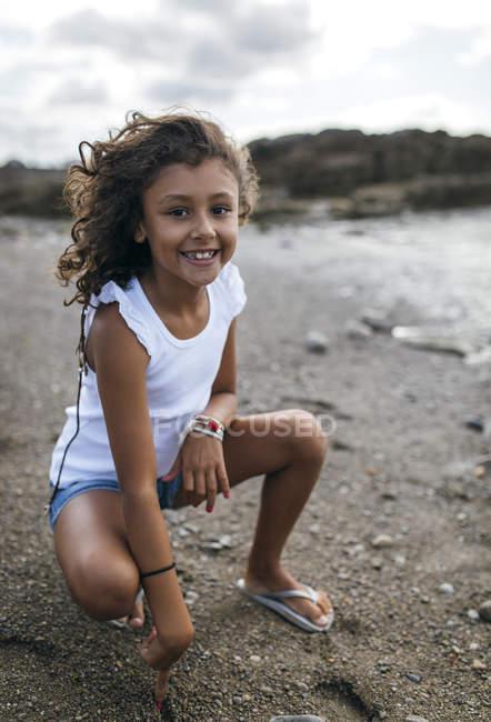 Portrait d'une petite fille souriante accroupie sur la plage — Photo de stock