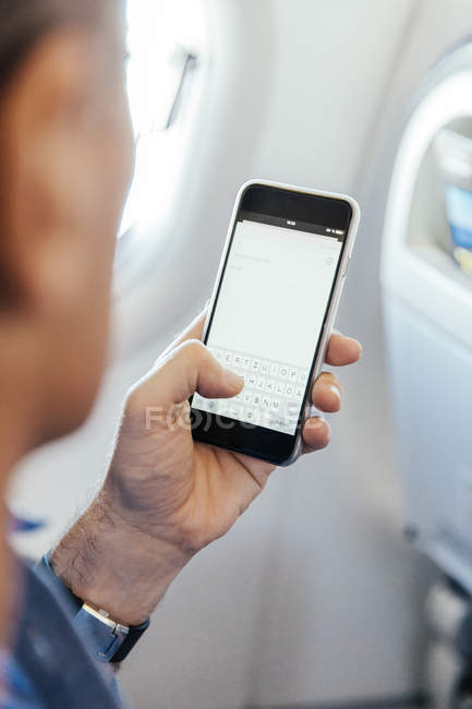 Mann sitzt in einem Flugzeug auf seinem Smartphone eingeben — Stockfoto