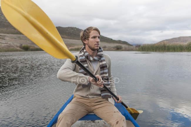 Jeune homme pagayant sur un lac — Photo de stock