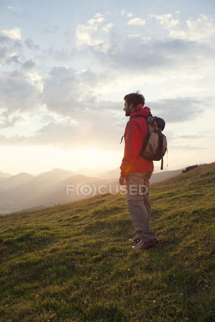 Austria, Tyrol, Unterberghorn, hiker standing in alpine landscape at sunrise — Stock Photo