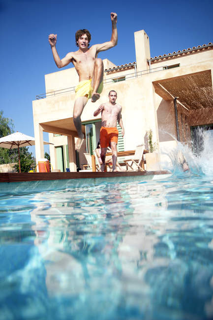 Young men jumping into swimming pool in summer — Stock Photo