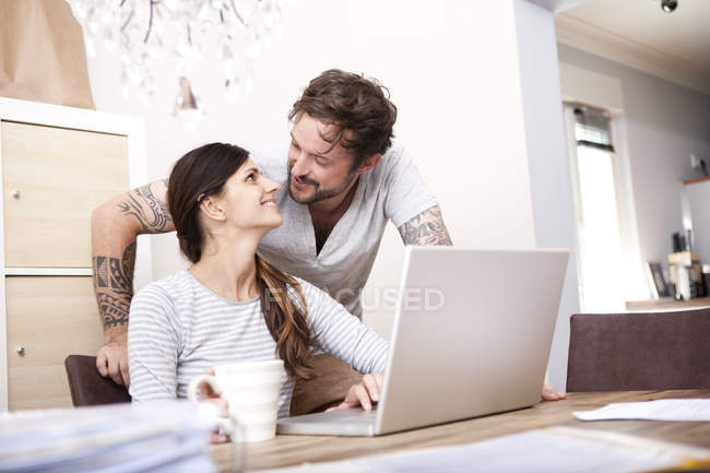 Happy couple together at home using laptop — Stock Photo