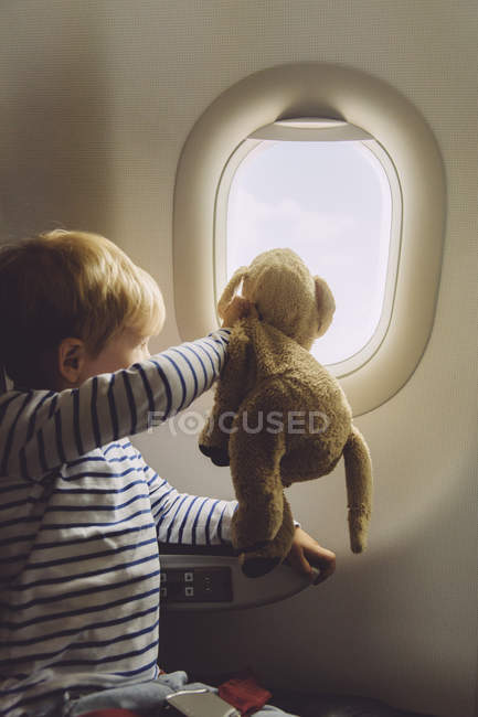 Menino sentado em um avião com seu brinquedo macio olhando pela janela — Fotografia de Stock