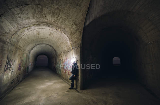Homem inclinado na parede em um garfo de dois túneis — Fotografia de Stock
