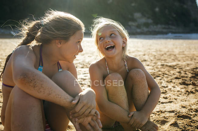 Two sisters having fun together on the beach — Stock Photo