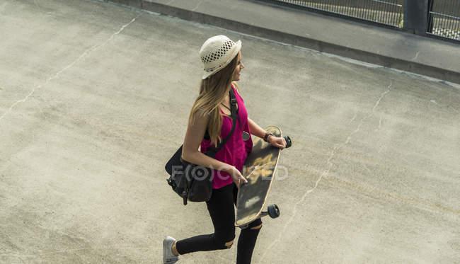 Adolescente marche avec planche à roulettes — Photo de stock