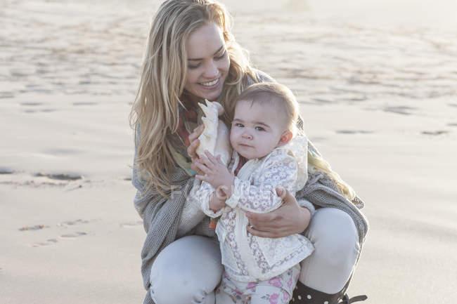 Матір та дитинча дівчина з оболонки на пляжі в красивою природою — стокове фото