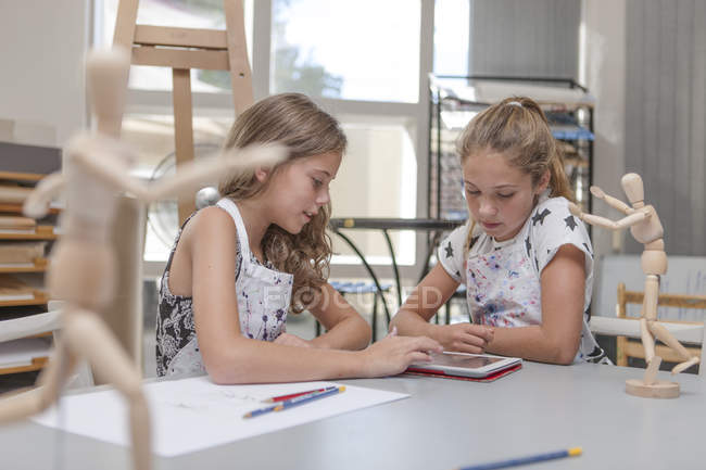 Zwei Mädchen mit digital-Tablette in eine Kunst-Klasse, die am Tisch sitzen — Stockfoto