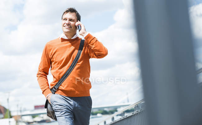 Businessman with shoulder bag walking while talking on the phone — Stock Photo