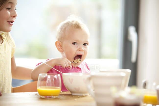 Девочка ест мюсли на завтрак таблице — стоковое фото
