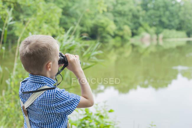 Мальчик с биноклем наблюдает за животными — стоковое фото
