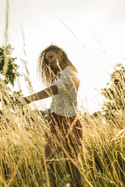 Woman touching tall grass in field — Stock Photo