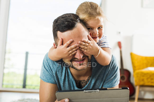 Daughter covering father's eyes — Stock Photo