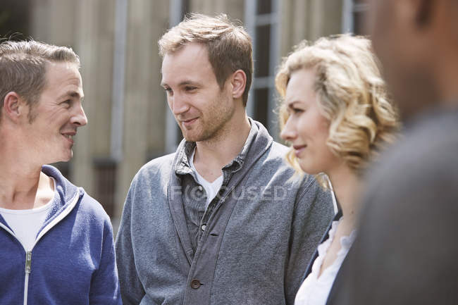 Cheerful friends smiling and talking in city street — Stock Photo