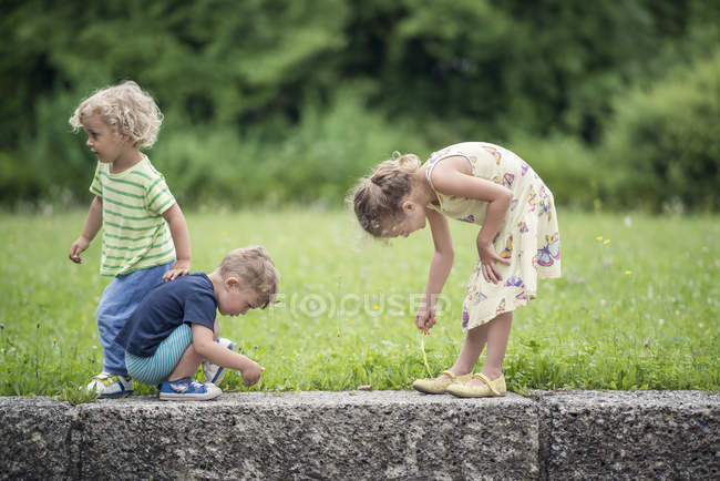 Three little children playing together outdoors — Stock Photo