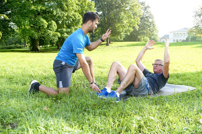 Man doing strength training on a meadow while his personal trainer watching him — Stock Photo