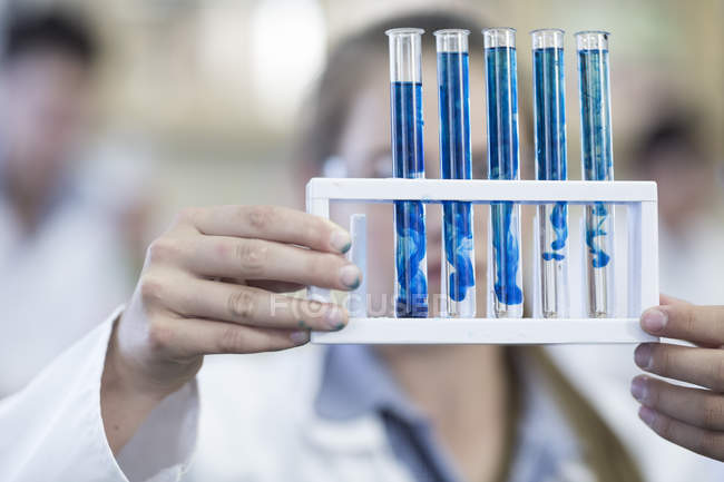 Close up of Girl in chemistry class holding test tube rack — Stock Photo