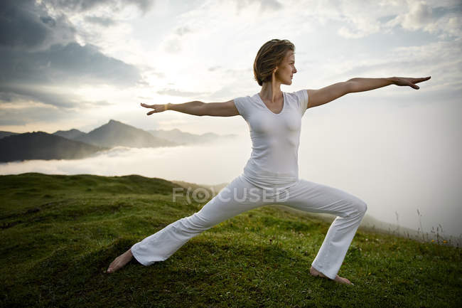 Austria. Kranzhorn, Mid adult woman practising yoga on mountain top — стоковое фото