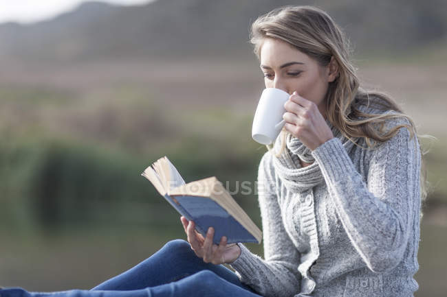 Frau mit Buch trinkt Kaffee auf einem Steg am See — Stockfoto