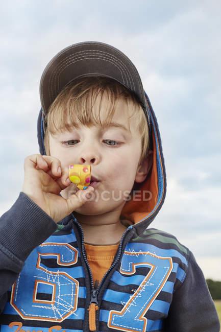 Портрет маленького мальчика с праздничным выдувом — стоковое фото