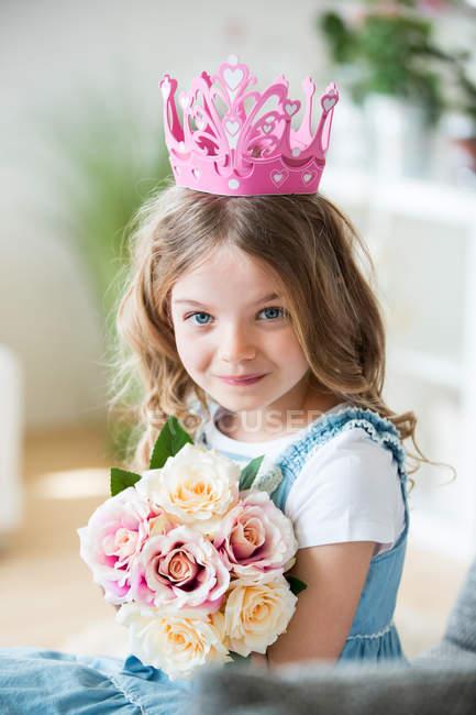 Дівчина носити рожеві корони проведення букет квітів на дому — стокове фото