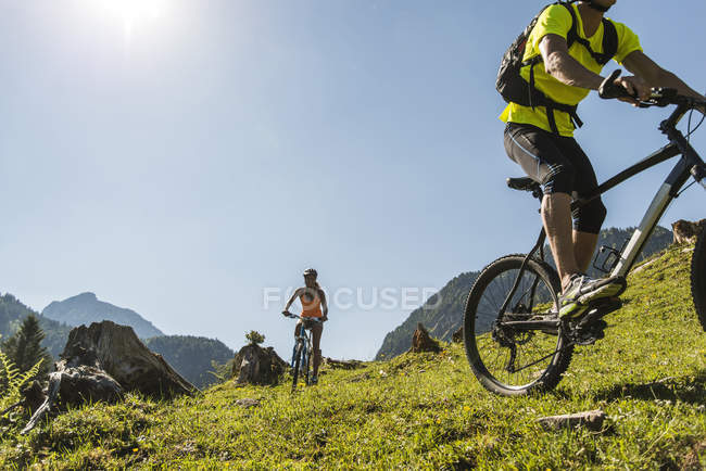 Austria, Tyrol, Tannheim Valley, young couple on mountain bikes in alpine landscape — Stock Photo