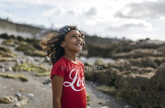 Portrait d'une petite fille souriante sur une plage rocheuse levant les yeux — Photo de stock