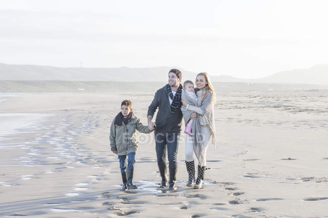 Молода пара з двома дітьми, прогулянки по пляжу — стокове фото